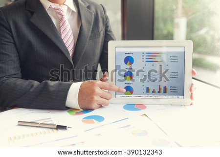 Attractive Businessman Meeting/present on tablet to discuss the situation on the market with product this year. - stock photo