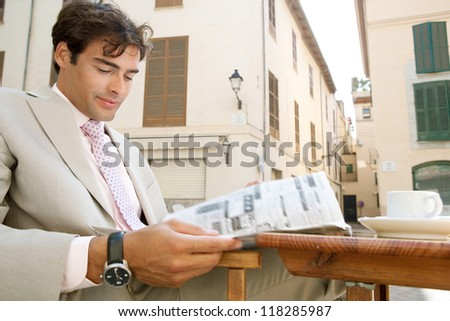Attractive businessman reading the classified adverts section of a newspaper in a coffee shop terrace table in a classic city, outdoors. - stock photo