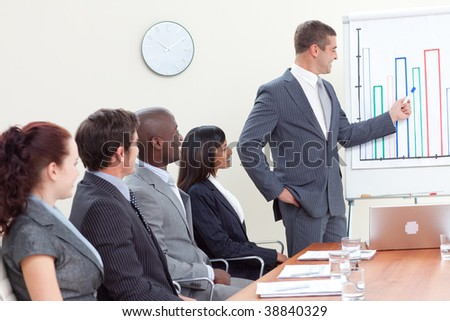 Attractive businessman reporting to sales figures to his team - stock photo