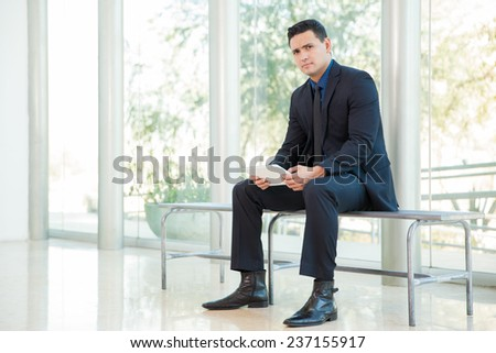 Attractive businessman sitting on a bench and using a tablet computer at work - stock photo