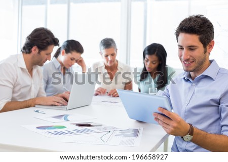 Attractive businessman smiling while using a tablet device in the office with coworkers behind - stock photo