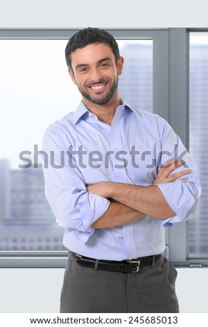 attractive businessman standing in corporate portrait smiling with folded arms in smart casual shirt and suit trousers in front of office window business district view in work and success concept - stock photo