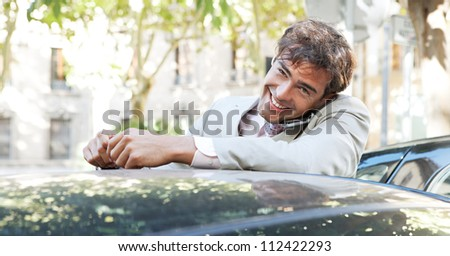 Attractive businessman using a cell phone and having a conversation while leaning on a car in the city. - stock photo