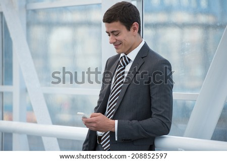 Attractive businessman using his smartphone in office building - stock photo