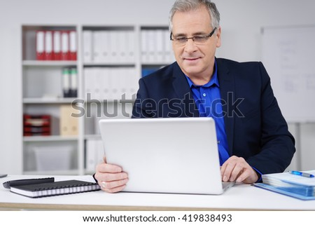 Attractive businessman working at his desk in the office on a laptop computer reading information on the screen with a serious expression - stock photo