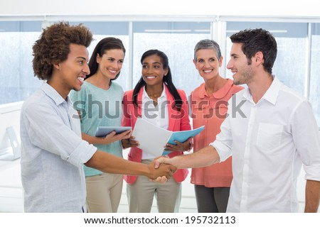 Attractive businessmen shaking hands at work in front of coworkers - stock photo