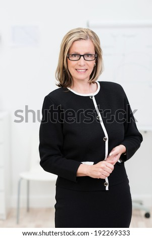 Attractive businesswoman dressed in black wearing glasses standing with clasped hands smiling at the camera - stock photo