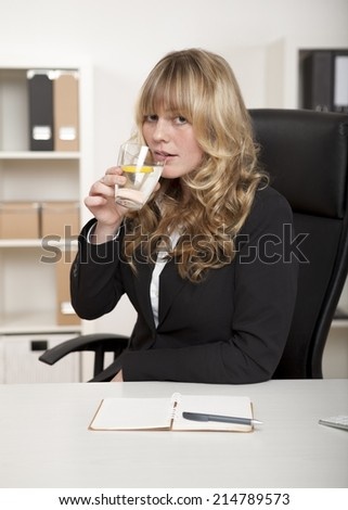 Attractive businesswoman drinking a glass of refreshing water with a slice of tangy lemon as she sits at her desk in the office - stock photo