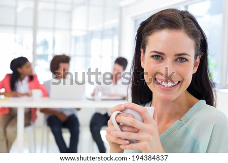 Attractive businesswoman drinking coffee with coworkers in background in the office - stock photo