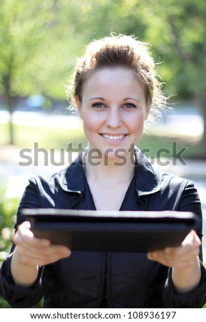 Attractive Businesswoman Handing Over Portfolio - stock photo