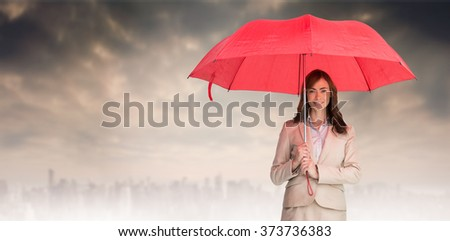 Attractive businesswoman holding red umbrella against dusty path leading to large city - stock photo
