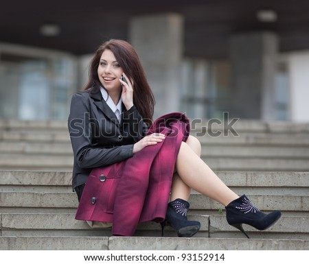 Attractive businesswoman on open air. Girl sitting on stairs talking on the phone - stock photo