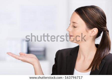 Attractive businesswoman or saleslady standing sideways looking at her empty palm which she is holding extended for your product placement or advertising - stock photo