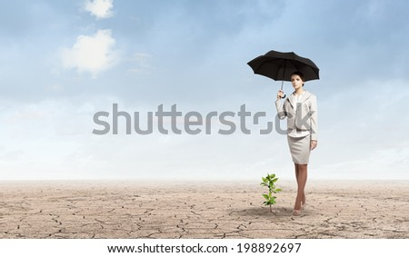 Attractive businesswoman protecting green sprout with umbrella - stock photo