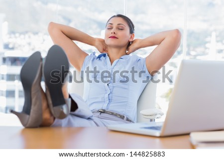 Attractive businesswoman relaxing in her office with her foot on the desk - stock photo