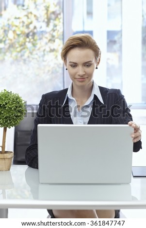 Attractive businesswoman sitting at desk, working with laptop computer. - stock photo