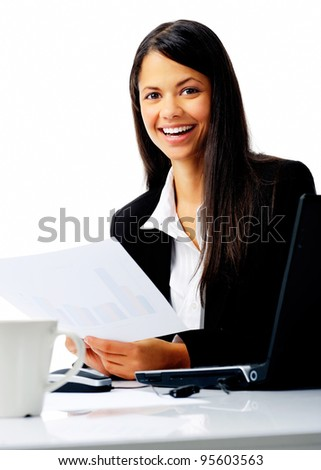 attractive businesswoman sitting at her desk, reading stats and graphs on paperwork while enjoying a cup of coffee and smiling isolated on white - stock photo