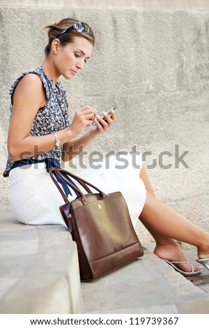 Attractive businesswoman sitting down on stone steps in the city, using a smart phone. - stock photo