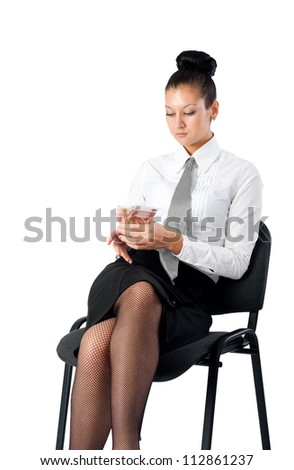 Attractive businesswoman sitting on chair with currency. Isolated on white - stock photo