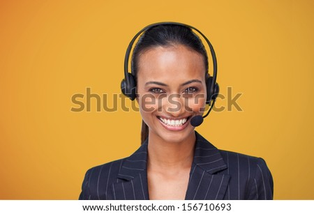 Attractive businesswoman smiling at camera on orange background - stock photo