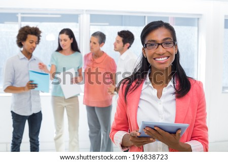 Attractive businesswoman smiling at camera while colleagues are standing behind in the office - stock photo