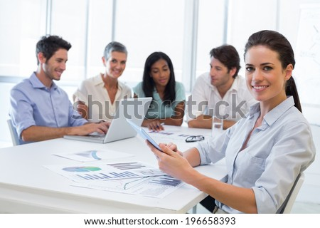 Attractive businesswoman smiling at the camera during a business meeting while using a tablet - stock photo