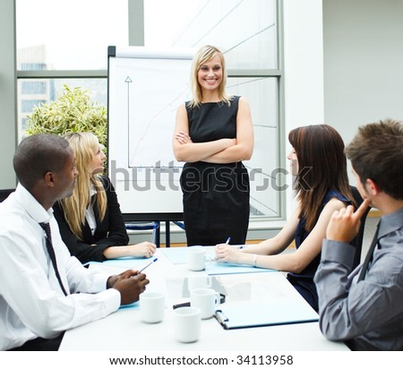 Attractive businesswoman standing in a meeting with folded arms - stock photo