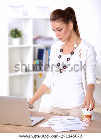 Attractive businesswoman standing  near desk in office - stock photo