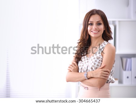 Attractive businesswoman standing near desk in the office - stock photo
