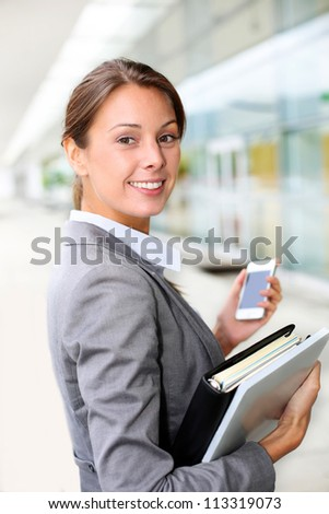 Attractive businesswoman standing outside - stock photo