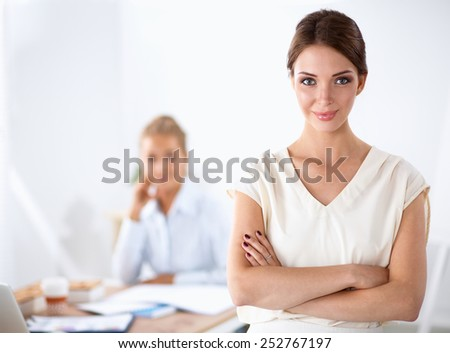 Attractive businesswoman with her arms crossed standing - stock photo