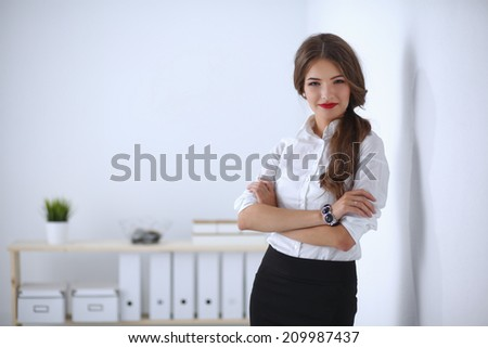 Attractive businesswoman with her arms crossed  standing in office - stock photo