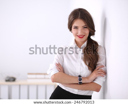 Attractive businesswoman with her arms crossed stnding - stock photo