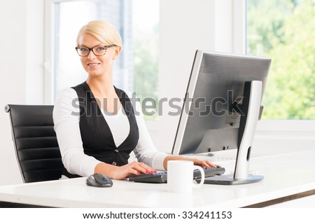 Attractive businesswoman working in the office by the computer, - stock photo