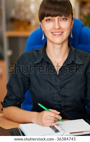 Attractive businesswoman writing in notebook in an office environment - stock photo