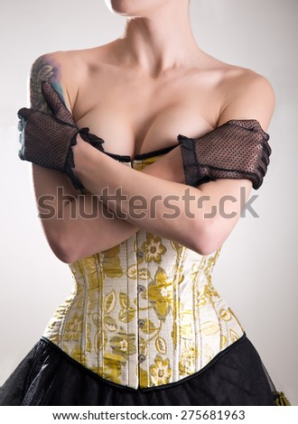 Attractive cabaret girl in corset embracing herself, studio shot on white background  - stock photo
