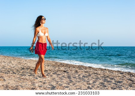 Attractive Caucasian brunette woman in her thirties in bikini walking alone on the beach in a summer sunny day - stock photo
