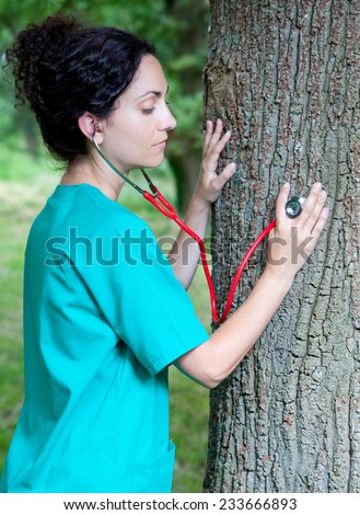 Attractive Caucasian brunette woman in medical uniform auscultating a trunk tree in a forest as a symbol of taking care of nature - stock photo