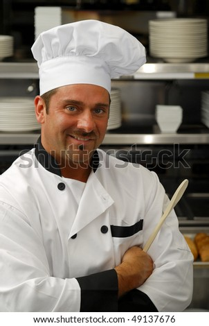 Attractive Caucasian chef holding a wooden spoon in a restaurant kitchen. - stock photo