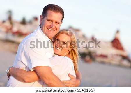 Attractive Caucasian Couple Hugging at the Beach in Front of the Hotel Del Coronado, San Diego, CA. - stock photo