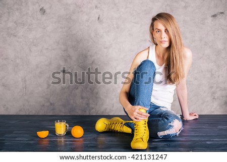 Attractive caucasian girl sitting on wooden surface with orange juice and fruit on concrete wall background - stock photo