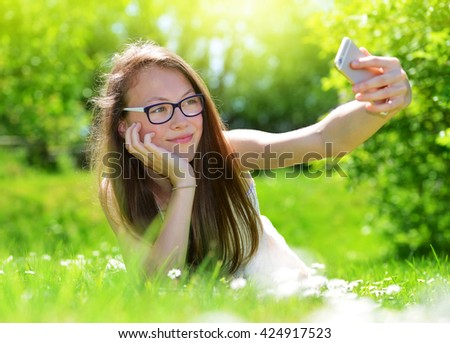 Attractive caucasian girl taking a selfie. Girl lying in the grass with smartphone. - stock photo