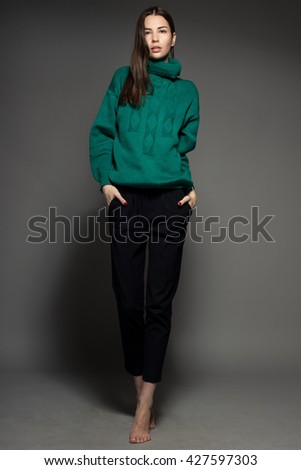 Attractive Caucasian happy sexy female model with brunette hair is moving in studio, wearing green sweater, isolated on dark background - stock photo
