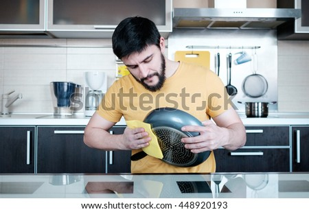 Attractive caucasian man cleaning the dripping pan in the kitchen - stock photo