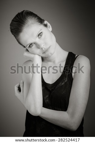 Attractive caucasian woman in her 30 isolated on a grey background, black and white image - stock photo
