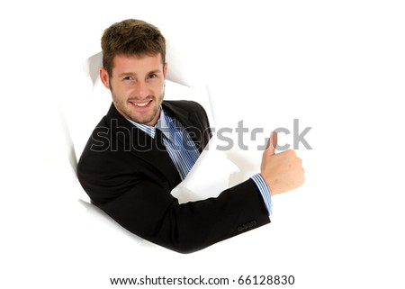 Attractive caucasian young businessman breaking through a paper wall showing thumb up. Happy face. Studio shot. White background - stock photo