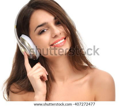 Attractive cheerful brunette woman listening and enjoying music in gold headphones smiling laughing and looking at camera isolated on a white background - stock photo
