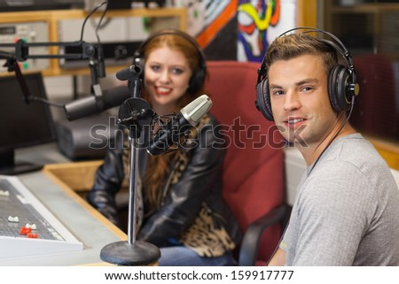 Attractive cheerful radio host interviewing a guest in studio at college - stock photo