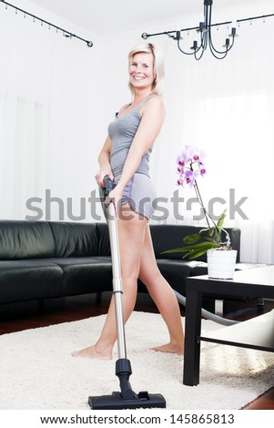 Attractive cheerful woman is in the room with vacuum-cleaner. - stock photo