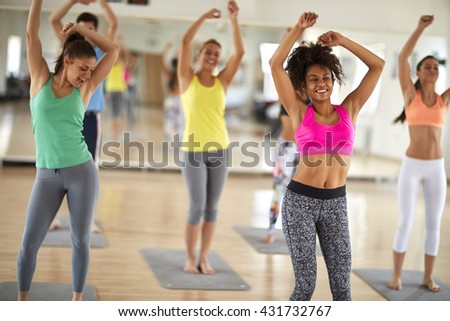 Attractive cheerful women dance at gym in colorful sportswear - stock photo